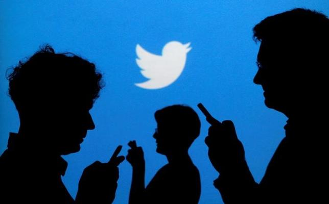 FILE PHOTO --  People holding mobile phones are silhouetted against a backdrop projected with the Twitter logo in this illustration picture taken in  Warsaw September 27, 2013.   REUTERS/Kacper Pempel/Illustration/File Photo