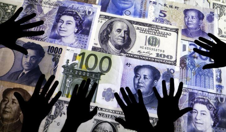 Hands are silhouetted against a backdrop projected with the picture of various currencies of money in this illustration taken April 4, 2016. REUTERS/Kacper Pempel/Illustration/Files