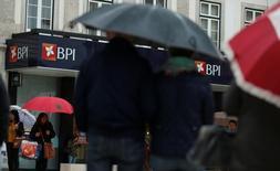 El consejo de BPI considera que la OPA de Caixabank es adecuada y amistosa, pero la dirección del banco luso valoró la entidad a 1,38 euros por acción, un 22 por ciento más de lo que ofrece el banco catalán. En la imagen, varias personas pasan junto a una sucursal de BPI en Lisboa, el 11 de mayo de 2016.  REUTERS/Rafael Marchante