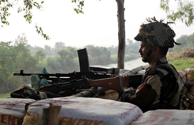 An Indian army soldier keeps guard from a bunker near the border with Pakistan in Abdullian, southwest of Jammu, September 30, 2016. REUTERS/Mukesh Gupta/Files