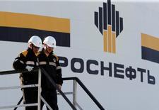 trabajadores caminan junto al logo de la compañía Rosneft en una de sus plantas en Nefteyugansk, Rusia. 4 de agosto de 2016. Un grupo liderado por la gigante rusa Rosneft comprará la refinería india Essar Oil por entre 12.000 y 13.000 millones de dólares, incluyendo deuda, dijeron fuentes cercanas al acuerdo, a fin de reforzar los lazos entre el mayor productor mundial de petróleo y el consumidor global de combustible de más rápido crecimiento. REUTERS/Sergei Karpukhin/File Photo