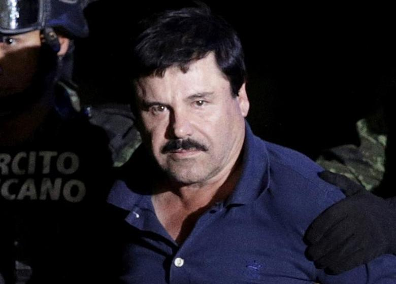 Recaptured drug lord Joaquin ''El Chapo'' Guzman is escorted by soldiers at the hangar belonging to the office of the Attorney General in Mexico City, Mexico January 8, 2016. REUTERS/Henry Romero/File Photo
