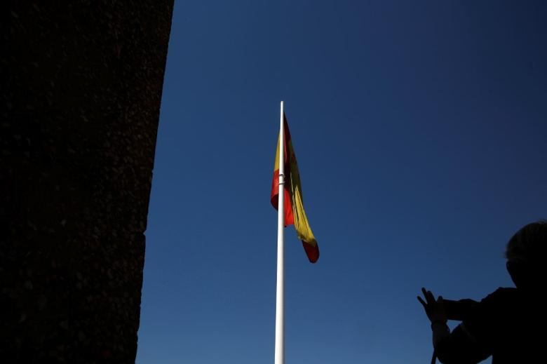 A woman takes pictures of a Spanish flag in Plaza Colon (Columbus Square) in Madrid, Spain, August 8, 2016. REUTERS/Susana Vera