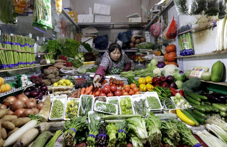 A vendor reaches out for vegetables at her shop in a market in Beijing February 18, 2016. REUTERS/Jason Lee/File Photo