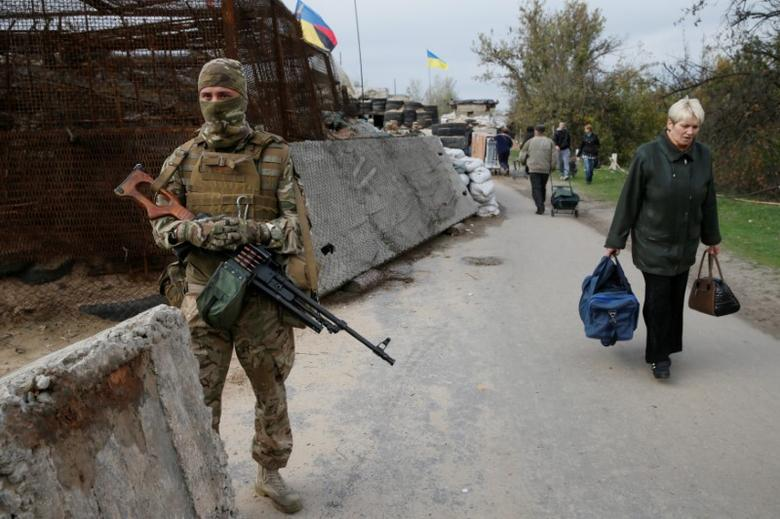 A member of  the Ukrainian armed forces stands guard as residents walk through a check point located on the contact line between pro-Moscow rebels and Ukrainian troops, in the settlement of Stanytsia Luhanska in Luhansk region, Ukraine.  REUTERS/Valentyn Ogirenko