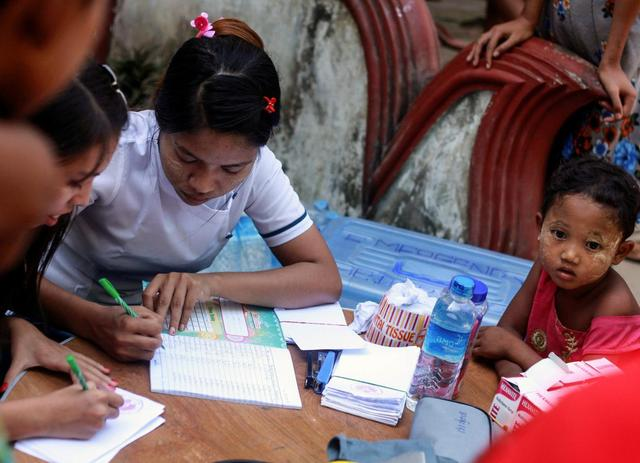 Volunteers from a local medical clinic help out in a medical check for internally displaced persons (IDP) who fled from recent violence in Maungdaw at a monastery in Sittwe, Myanmar October 15, 2016.  REUTERS/Wa Lone