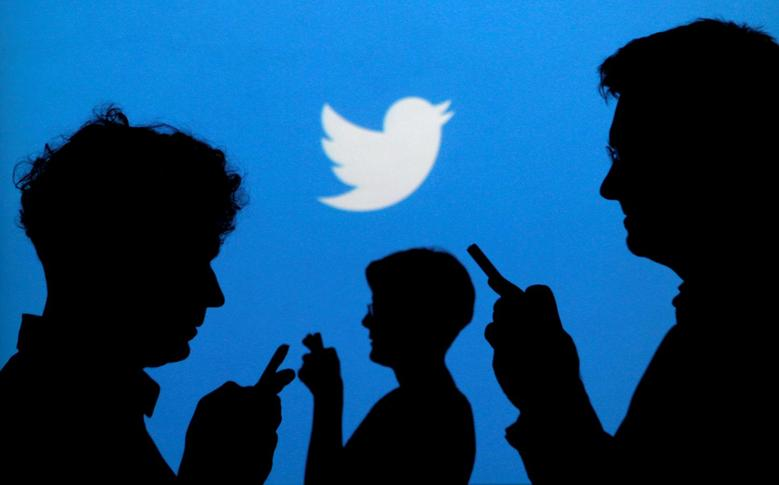 FILE PHOTO: People holding mobile phones are silhouetted against a backdrop projected with the Twitter logo in this illustration picture taken September 27, 2013. REUTERS/Kacper Pempel/Illustration/File Photo