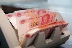 Fotografía de archivo de billetes de 100 yuan en un máquina contadora en el banco comercial de Pekín, el 30 de marzo, 2016 . El yuan en el mercado extranjero cayó a un nuevo mínimo en seis años frente al dólar en las primeras operaciones del lunes, en línea con la debilidad de la moneda en el mercado chino después de que el índice dólar alcanzó su nivel más alto en ocho meses. REUTERS/Kim Kyung-Hoon/File Photo