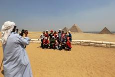 Туристы фотографируются на фоне пирамид в пригороде Каира 31 августа 2016 года. Египет надеется привлечь туристов из новых стран, таких как Китай, Япония и Украина, спустя год после того как Россия и Великобритания приостановили полеты в страну пирамид, сообщил глава египетского туристического ведомства. REUTERS/Mohamed Abd El Ghany