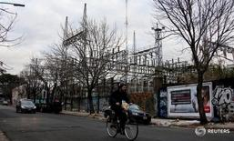 A man rides his bicycle past Edenor electric company power distribution plant in Buenos Aires, Argentina, August 5, 2015. For 13 years, a near blanket freeze on utility tariffs has pushed creaking power grids to the brink of collapse in Argentina's capital, stunting private investment and leading to regular outages when demand peaks. Now, with a presidential election looming, the biggest distributor Edenor is drawing up a new 10-year investment plan. The firm expects a government led by either of the main candidates - the ruling party's Daniel Scioli and his more business-friendly rival Mauricio Macri - will lift rates. To match story ARGENTINA-ELECTION/UTILITIES  REUTERS/Marcos Brindicci - RTX1N7YI