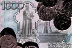 Рублевые монеты и купюра 7 июня 2016 года. Рубль торговался в плюсе на биржевой сессии вторника благодаря поддержке экспортеров, которые, впрочем, сократили к вечеру присутствие на рынке и в целом не сильно увеличили активность к пику налоговых выплат, продавая выручку равномерно в течение месяца. REUTERS/Maxim Zmeyev/Illustration