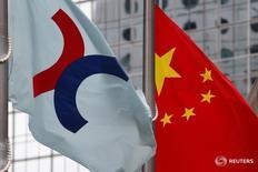 Флаги Гонконгской фондовой биржи (слева) и КНР в Гонконге 7 июня 2016 года. Китайские фондовые индексы снизились по итогам торгов понедельника, настроения инвесторов омрачили предупреждения политиков об экономических пузырях и неопределенность вокруг президентских выборов в США.  REUTERS/Bobby Yip/File Photo