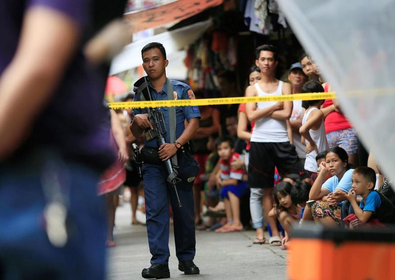 A member of the Philippine National Police (PNP) stands guard while residents look on near the scene where two suspected drug pushers were killed during a police operation, in metro Manila, Philippines October 8, 2016. REUTERS/Romeo Ranoco