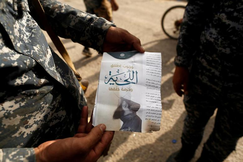 An Iraqi soldier shows a pamphlet which reads ''Wearing beards is compulsory, shaving is prohibited'' along a street of the town of al-Shura, which was recaptured from Islamic State (IS) on Saturday, south of Mosul, Iraq October 30, 2016. REUTERS/Zohra Bensemra/File Photo