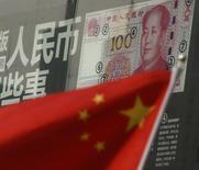Una bandera china frente a un billete de 100 yuanes, en una sucursal de un banco en un distrito comercial en Pekín, China. 21 de agosto de 2016. Las acciones chinas avanzaron el jueves después de que una encuesta privada mostró más señales de estabilidad económica. REUTERS/Kim Kyung-Hoon