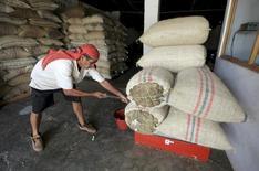 Un trabajador pesa el café en una bodega de Pueblo Bello, Colombia 29 de Enero, 2014. Colombia redujo su déficit comercial en 24,8 por ciento en septiembre frente a igual mes del año pasado, a 1.065,4 millones de dólares, en vista de que el valor de las exportaciones disminuyó en la mitad de lo que bajó el de las importaciones, revelaron el viernes cifras del Departamento Nacional de Estadísticas (DANE).REUTERS/Jose Miguel Gomez