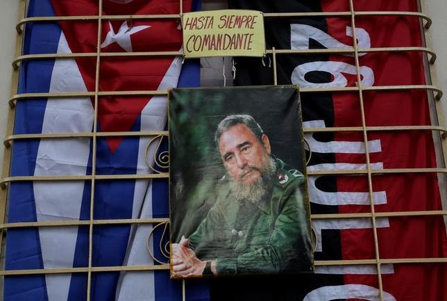 11月26日、キューバのフィデル・カストロ前国家評議会議長が前日夜、死去した。90歳だった。同国の国旗とカストロ氏の写真、キューバのアルテミサ州で27日撮影(2016年 ロイター)