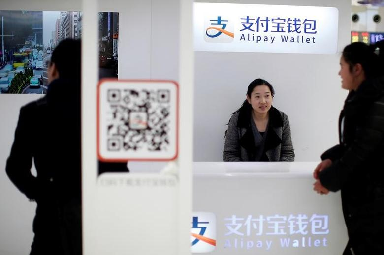A sales assistant sits behind and under Alipay logos at a train station in Shanghai, February 9, 2015. REUTERS/Aly Song/Files
