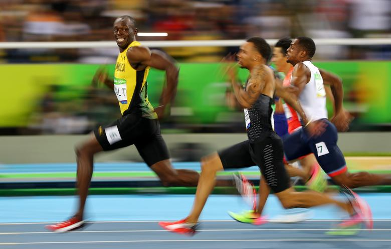 Usain Bolt of Jamaica turns to look at Andre De Grasse of Canada as they compete in the Men's 100m Semifinals at the 2016 Rio Olympics in Brazil, August 14, 2016. REUTERS/Kai Pfaffenbach