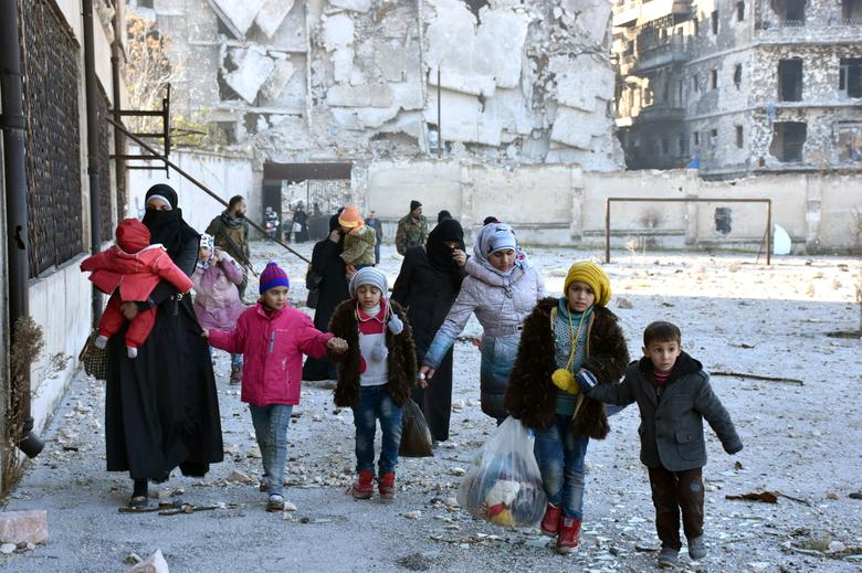 Civilians, who evacuated the eastern districts of Aleppo, carry their belongings as they arrive in a government held area of Aleppo, Syria, in this handout picture provided by SANA on December 7, 2016. SANA/Handout via REUTERS