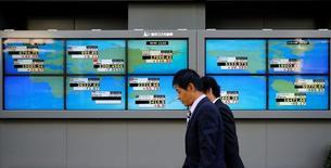Hombres caminan frente a unas pantallas que muestra el índice Nikkei y otras divisas afuera de una correduría en Tokio, Japón. 6 de julio de 2016.El índice Nikkei de la bolsa de Tokio saltó el viernes a su nivel más alto en un año, apoyado por las ganancias en Wall Street y el avance de las acciones de los exportadores ante la debilidad del yen.   REUTERS/Toru Hanai