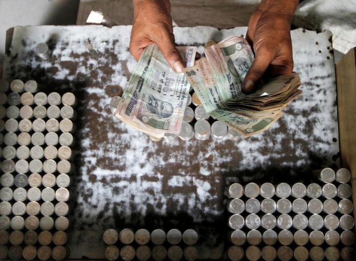 A man exchanging damaged Indian currency counts 100 rupee notes along a roadside in Kolkata August 30, 2013.   REUTERS/Rupak De Chowdhuri/File Photo