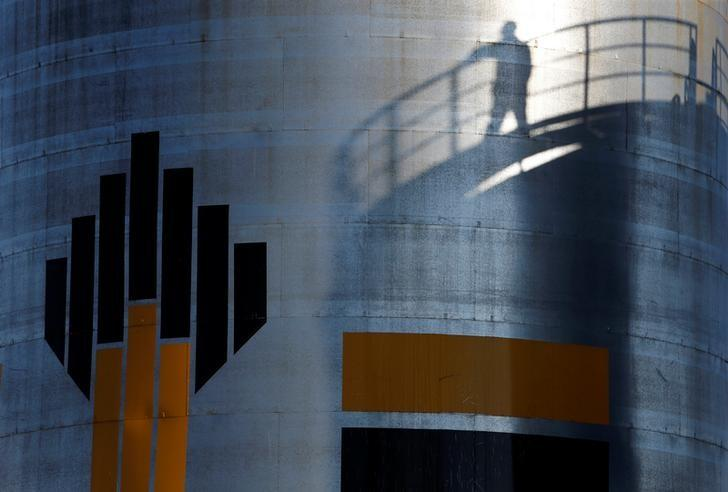 The shadow of a worker is seen next to the logo of Russia's Rosneft oil company at the central processing facility of the Rosneft-owned Priobskoye oil field outside the city of Nefteyugansk, Russia, August 4, 2016. REUTERS/Sergei Karpukhin/Files