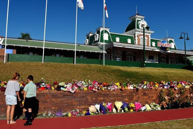 Members of the public leave floral tributes outside the main entrance to Dreamworld located on the Gold Coast, Australia October 26, 2016 after the tragedy that saw four people killed on the Thunder River Rapids Ride at Australia's biggest theme park. AAP/Dan Peled/via REUTERS/Files