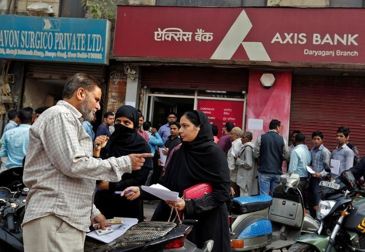 People prepare documents outside a branch of Axis Bank before queueing to exchange old high denomination bank notes in Old Delhi, India, November 10, 2016. REUTERS/Cathal McNaughton