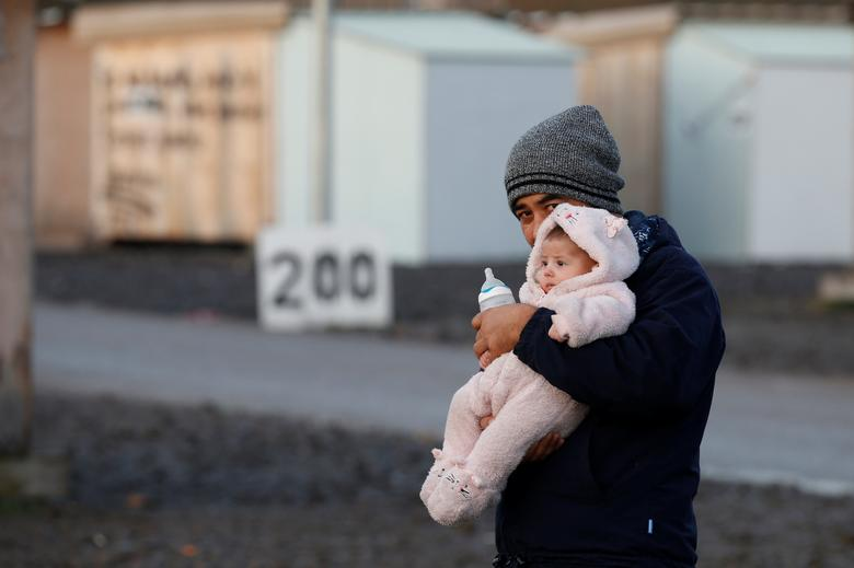 An afghan migrant and his baby are pictured in a camp for migrants in Grande-Synthe, France December 14, 2016. REUTERS/Pascal Rossignol
