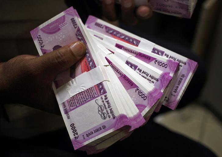 A cashier displays the new 2,000 rupee banknotes inside a bank in Jammu, November 15, 2016. REUTERS/Mukesh Gupta/Files