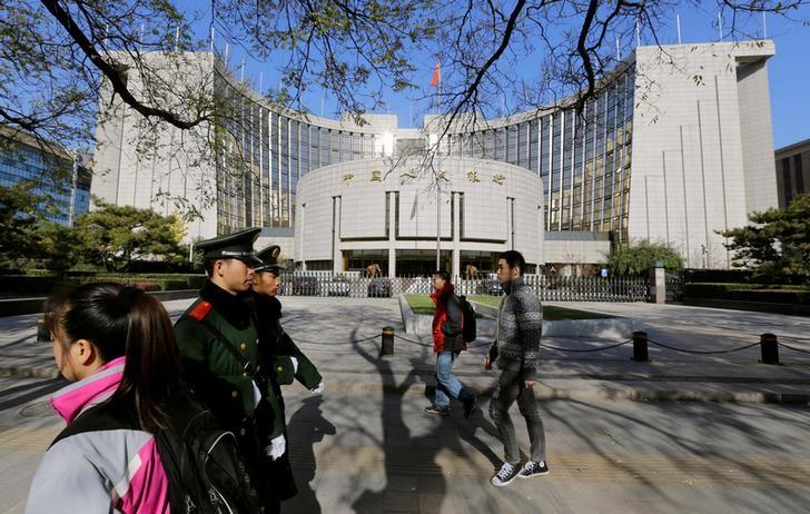 People walk past the headquarters of the People's Bank of China (PBOC), the central bank, as two paramilitary police officials patrol around it in Beijing November 20, 2013.   REUTERS/Jason Lee/File Photo