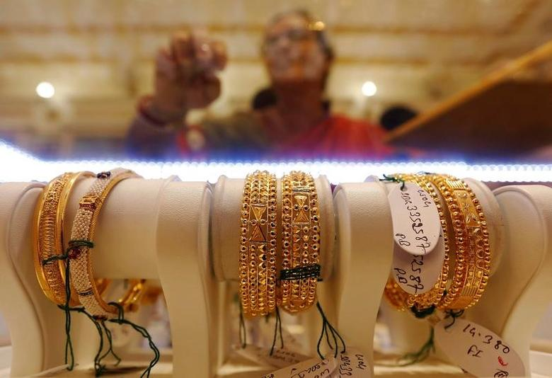 Gold bangles are on display as a woman makes choices at a jewellery showroom during Dhanteras, a Hindu festival associated with Lakshmi, the goddess of wealth, in Kolkata, India October 28, 2016. REUTERS/Rupak De Chowdhuri