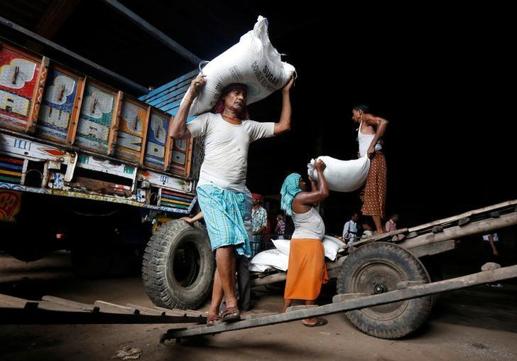 Labourer carry sacks filled with sugar to load them onto a supply truck at a wholesale market in Kolkata, India May 16, 2016. REUTERS/Rupak De Chowdhuri/Files