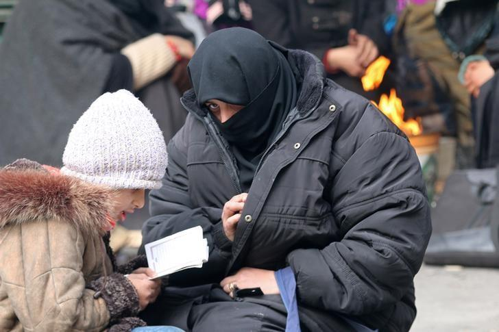 A woman sits with her child reading the Koran while waiting to be evacuated with others from a rebel-held sector of eastern Aleppo, Syria December 17, 2016. REUTERS/Abdalrhman Ismail