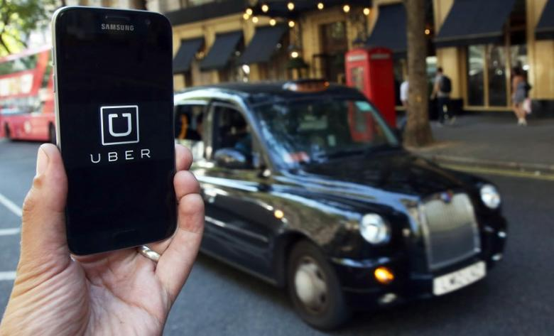 A photo illustration shows the Uber app logo displayed on a mobile telephone, as it is held up for a posed photograph in central London, Britain August 17, 2016.    REUTERS/Neil Hall/Illustration/File Photo - RTX2P60S