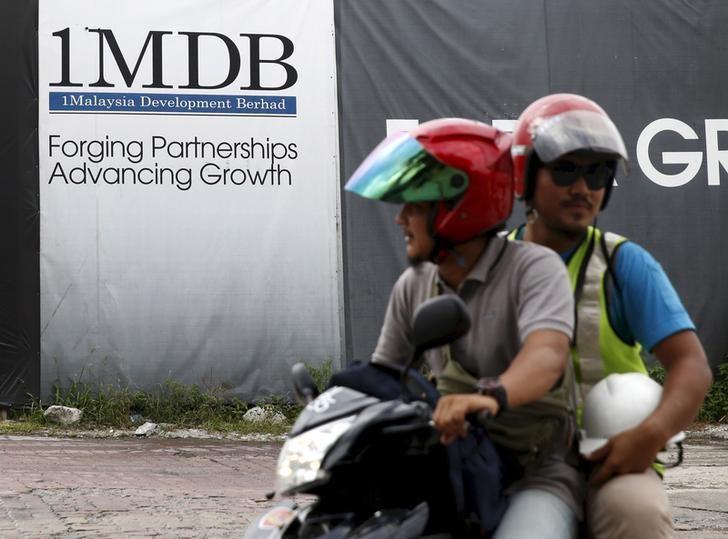 Motorcyclists pass a 1Malaysia Development Berhad (1MDB) billboard at the Tun Razak Exchange development in Kuala Lumpur, Malaysia, February 3, 2016. REUTERS/Olivia Harris/File Photo