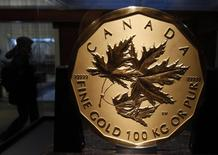 A visitor to the Royal Canadian Mint passes a 100 kilogram solid gold coin during the Vancouver 2010 Winter Olympics February 13, 2010.     REUTERS/Chris Helgren