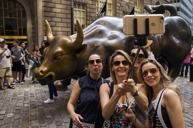 Tourists pose for photographs with a landmark statue of a bull in New York, U.S. on August 24, 2015. REUTERS/Lucas Jackson/File Photo
