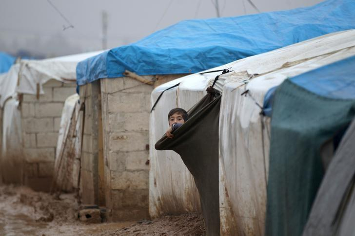 An internally displaced Syrian boy looks out his tent in the Bab Al-Salam refugee camp, near the Syrian-Turkish border, northern Aleppo province, Syria December 26, 2016. REUTERS/Khalil Ashawi