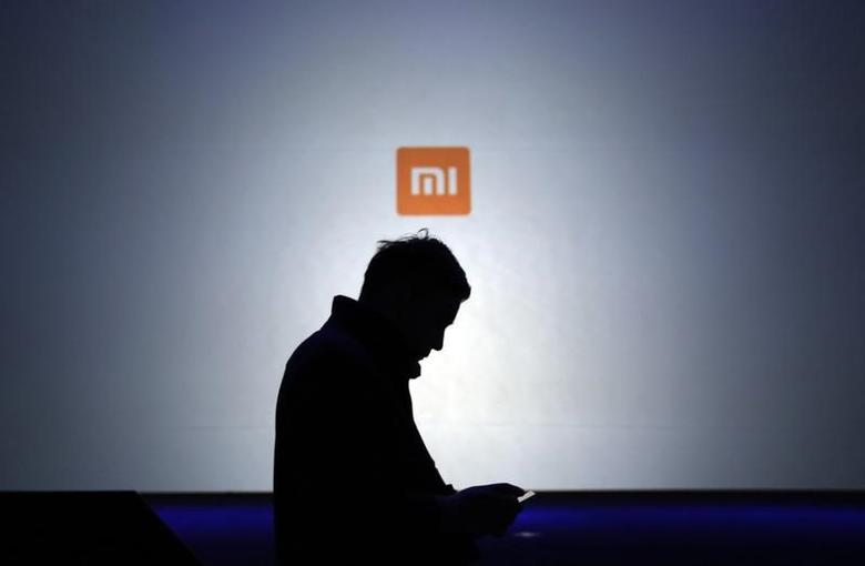 A man uses his mobile phone in front of a screen showing a logo of Xiaomi at the launch ceremony of the Mi Note in Beijing, January 15, 2015.  REUTERS/Jason Lee