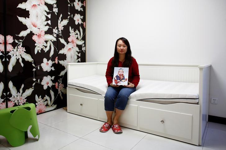 Dai Xiaolei poses with a picture of her son in the bedroom she designed for him in her former marital apartment in Beijing, China, September 19, 2016. Picture taken September 19, 2016.  REUTERS/Thomas Peter