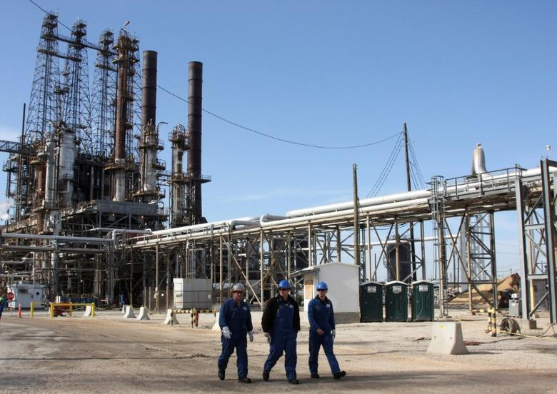 FILE PHOTO - Refinery workers walk inside the LyondellBasell oil refinery in Houston, Texas March 6, 2013. REUTERS/Donna Carson/File Photo