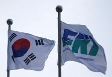 Le drapeau de la Fédération des industries coréennes (FKI) flotte au côté du drpeau national à Séoul. La Corée du Sud a revu à la baisse sa prévision de croissance pour 2017 jeudi face à la dégradation de la demande intérieure et au ralentissement du marché du travail, deux tendances qui freinent la reprise de la quatrième économie d'Asie. /Photo prise le 13 décembre 2016/REUTERS/Kim Hong-Ji