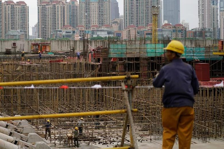 Labourers work at a construction site on the Bund in front of the financial district of Pudong in Shanghai, China October 19, 2016. REUTERS/Aly Song