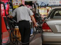 A gas station worker fuels a vehicle in Tokyo August 26, 2015. Crude oil futures edged up on Wednesday, but were still not far off 6-1/2 year lows after China's central bank moved to support the country's stumbling economy, while concerns about a supply glut capped gains.  REUTERS/Toru Hanai