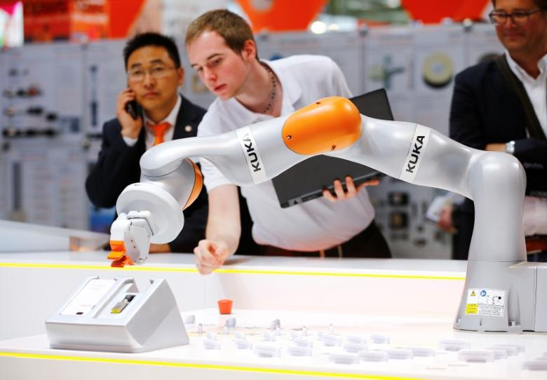 A Kuka technician programs a robot arm of German industrial robot maker Kuka at the company's stand during the Hannover Fair in Hanover, Germany, April 25, 2016.    REUTERS/Wolfgang Rattay