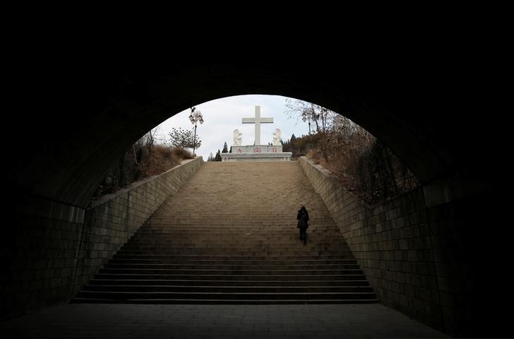 A villager climbs up the steps toward a cross near a Catholic church on the outskirts of Taiyuan, North China's Shanxi province, December 24, 2016. Picture taken on December 24, 2016. REUTERS/Jason Lee
