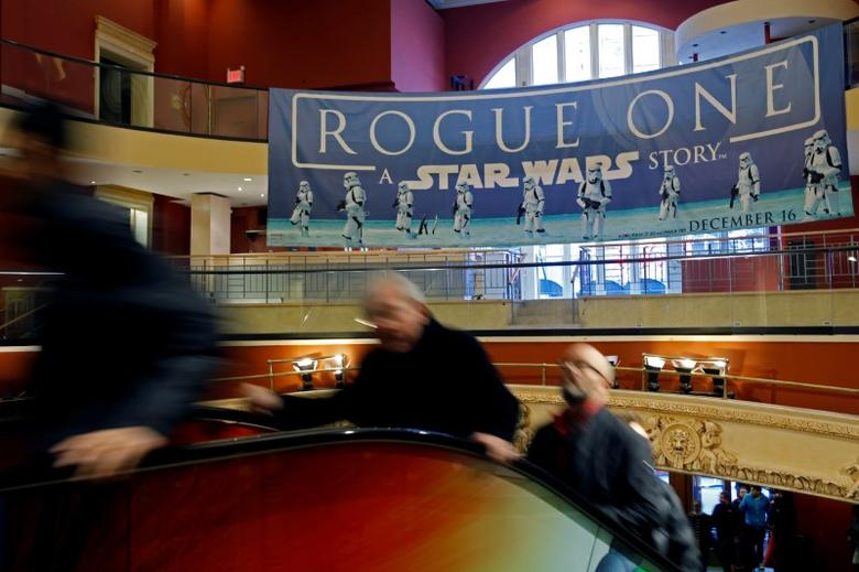 People ride an escalator under a Star Wars Rogue One poster at AMC Empire 25 on Christmas Day in Manhattan, New York City, U.S., December 25, 2016. REUTERS/Andrew Kelly