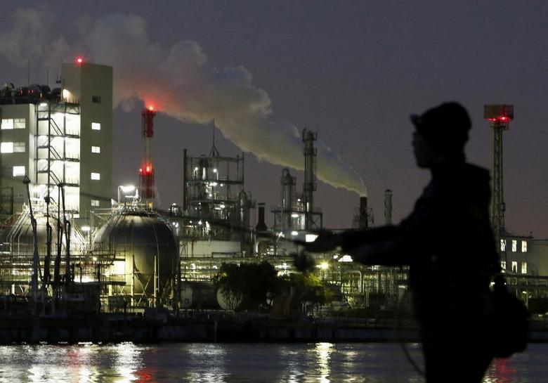 Smoke is emitted from a chimney as a man fishes at the Keihin industrial zone in Kawasaki, Japan, March 28, 2016.  REUTERS/Yuya Shino/File Photo